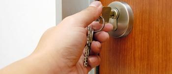 hand turning key in door lock