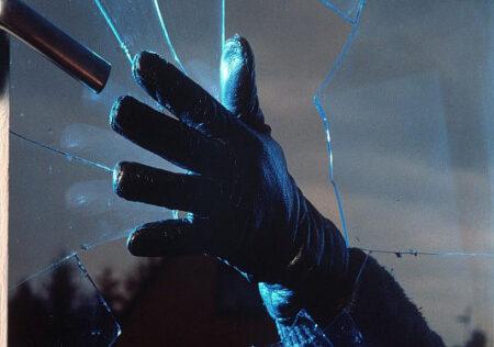 gloved hand breaking window